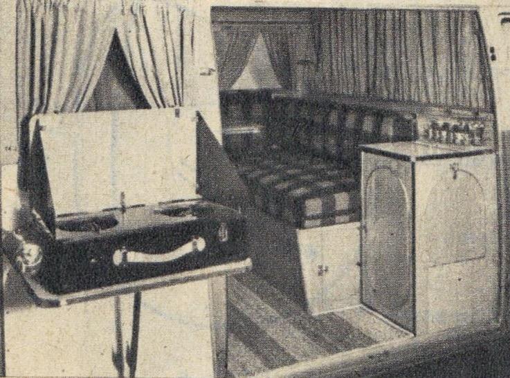 Le living room avec bar, table rabattable, bancs capitonnés. A l'intérieur, dans la porte ouverte, la cuisine.